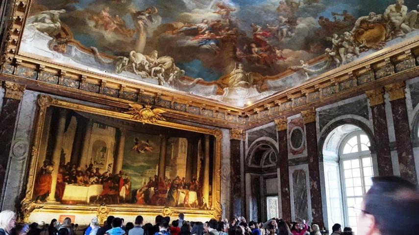 Perhatikan lukisan raksasa dengan orang di dekatnya, dan lukisan di atap